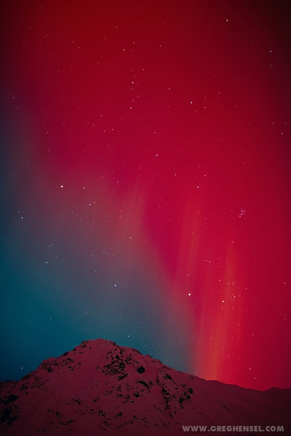 Red aurora over mountain at Hatcher Pass in the Matanuska Valley. Winter in Southcentral Alaska.