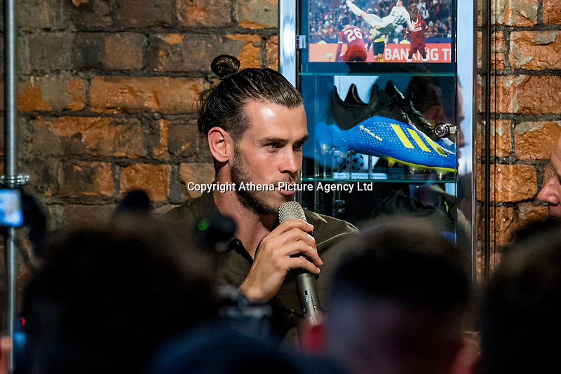 "Pictured: Gareth Bale at his Elevens Bar in Cardiff, Wales, UK. Thursday 12 July 2018<br /> Re: Last night (Thurday 12 July) Elevens Bar & Grill and the Football Association of Wales jointly hosted a Q&A evening with Gareth Bale. At the event, Gareth unveiled a new piece of memorabilia for Elevens – his match worn boots from this year's Champions League Final with which he scored that incredible overhead kick.<br /> The event, hosted at Elevens Bar & Grill was open to members of the public with doors opening at 6pm on Thursday evening. People started queueing from 3pm, with a cross-section of fans of all ages in Wales shirts and bucket hats. <br /> The Q&A, conducted by Ian Gwyn Hughes from the FAW, discussed all aspects of his career so far, from growing up in Cardiff to winning 4 Champions League medals with Real Madrid. On growing up in Whitchurch, Gareth said: ""My family were a huge influence on me growing up. My parents were so supportive, taking me here there and everywhere so I could play football. Growing up I can hardly remember not being with a football – I even took one to bed!""<br /> There were a lot of youngsters in the audience, eager to hear from their hero. Gareth's advice to them? ""Work hard for what you want and who knows where that could take you.""<br /> As a left-footer, Ryan Giggs,  Wales' national team manager was someone he looked up to growing up. Gareth mentioned it was great to beat Ian Rush's goal scoring record for Wales with his childhood idol as manager. ""I knew I'd levelled his record at half time, I needed one more to break it. The manager wanted to take me off but I said give me another 15 minutes to see if I can do it. Luckily on 61 minutes our goalkeeping coach took too long to do the substitution on the paper, so it gave me an extra minute. It worked out perfectly."""