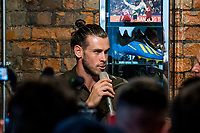 Pictured: Gareth Bale at his Elevens Bar in Cardiff, Wales, UK. Thursday 12 July 2018<br /> Re: Last night (Thurday 12 July) Elevens Bar &amp; Grill and the Football Association of Wales jointly hosted a Q&amp;A evening with Gareth Bale. At the event, Gareth unveiled a new piece of memorabilia for Elevens &ndash; his match worn boots from this year&rsquo;s Champions League Final with which he scored that incredible overhead kick.<br /> The event, hosted at Elevens Bar &amp; Grill was open to members of the public with doors opening at 6pm on Thursday evening. People started queueing from 3pm, with a cross-section of fans of all ages in Wales shirts and bucket hats. <br /> The Q&amp;A, conducted by Ian Gwyn Hughes from the FAW, discussed all aspects of his career so far, from growing up in Cardiff to winning 4 Champions League medals with Real Madrid. On growing up in Whitchurch, Gareth said: &ldquo;My family were a huge influence on me growing up. My parents were so supportive, taking me here there and everywhere so I could play football. Growing up I can hardly remember not being with a football &ndash; I even took one to bed!&rdquo;<br /> There were a lot of youngsters in the audience, eager to hear from their hero. Gareth&rsquo;s advice to them? &ldquo;Work hard for what you want and who knows where that could take you.&rdquo;<br /> As a left-footer, Ryan Giggs,  Wales&rsquo; national team manager was someone he looked up to growing up. Gareth mentioned it was great to beat Ian Rush&rsquo;s goal scoring record for Wales with his childhood idol as manager. &ldquo;I knew I&rsquo;d levelled his record at half time, I needed one more to break it. The manager wanted to take me off but I said give me another 15 minutes to see if I can do it. Luckily on 61 minutes our goalkeeping coach took too long to do the substitution on the paper, so it gave me an extra minute. It worked out perfectly.&rdquo;