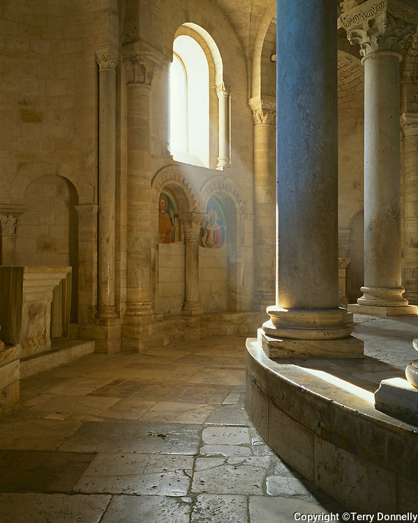Tuscany, Italy: Sun streaming on the Romanesque pillars and ambulatory of Abbazia di Sant' Antimo, a medieval abbey at Castelnuovo dell' Abate