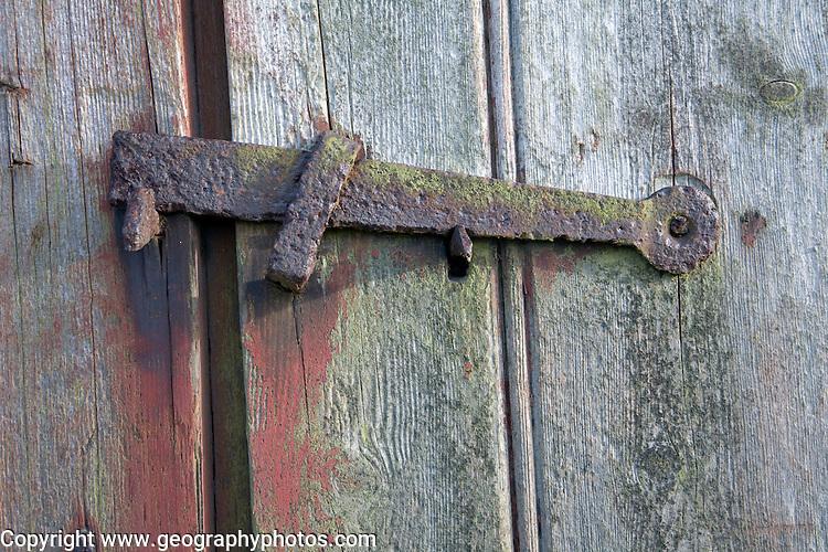 Rusty metal latch on wooden door