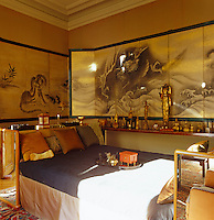 The Japanese hand-painted screen covering the bedroom walls dates from the 17th century and a large collection of small statues, including bronze buddhas from Thailand, can be seen on an adjacent antique table