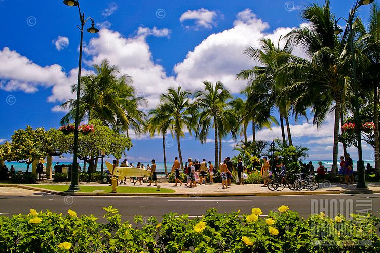 People enjoy a walk or bike ride along the palm tree lined and historic Kalakau Avenue that parallels beautiful Waikiki Beach,Oahu.