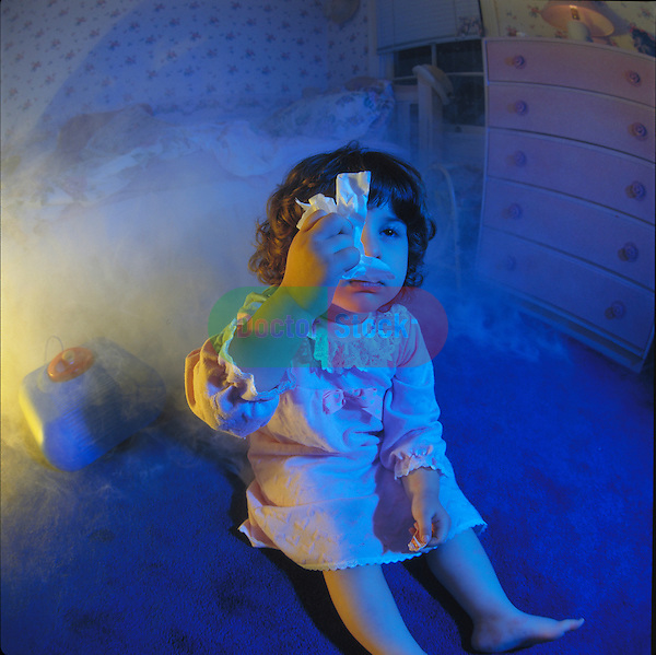 young child with a bad cold blowing nose, sitting on floor in bedroom with vaporizer