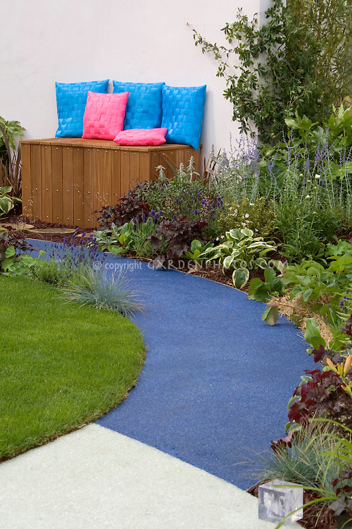 Garden bench and storage, curving patio path, lawn, perennials, colorful pillows, in modern backyard design