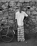 SRI LANKA, Asia, portrait of man standing by stone wall (B&W)