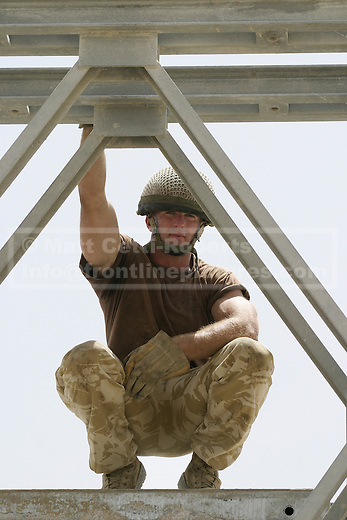 A Royal Engineer of 9 Parachute Squadron RE squats and looks through the side of bridge in the Rumaylah Oilfields. The bridge was built during the 2003 invasion of Iraq to replace a bombed out span.