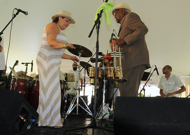 """Trumpeter, Alfredo """"Chocolate"""" Armenteros, dancing with  Zon del Barrio Orchestra vocalist Marryann Santiago, at the 2014 Jazz in the Valley Festival held in Waryas Park on the Hudson River front in Poughkeepsie, NY on Sunday August 17, 2014. Photo by Jim Peppler. Copyright Jim Peppler 2014 all rights reserved."""