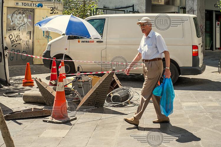 ATHENS, GREECE: a man walks close to a maintenance works site.