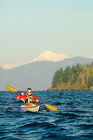 Male paddler in yellow kayak and red PFD paddling in San Juan Islands with Moutn Baker visible in background, Sea Kayaking the San Juan Islands, WA.