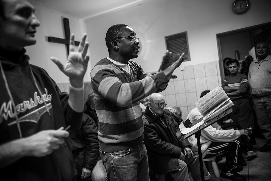 A Nigerian pastor leads a prayer meeting at Victory Outreach, a soup kitchen and shelter for the homeless in Bucharest.