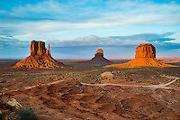 A setting sun paints the iconic buttes of Monument Valley located in the Navajo Nation of Utah/Arizona.