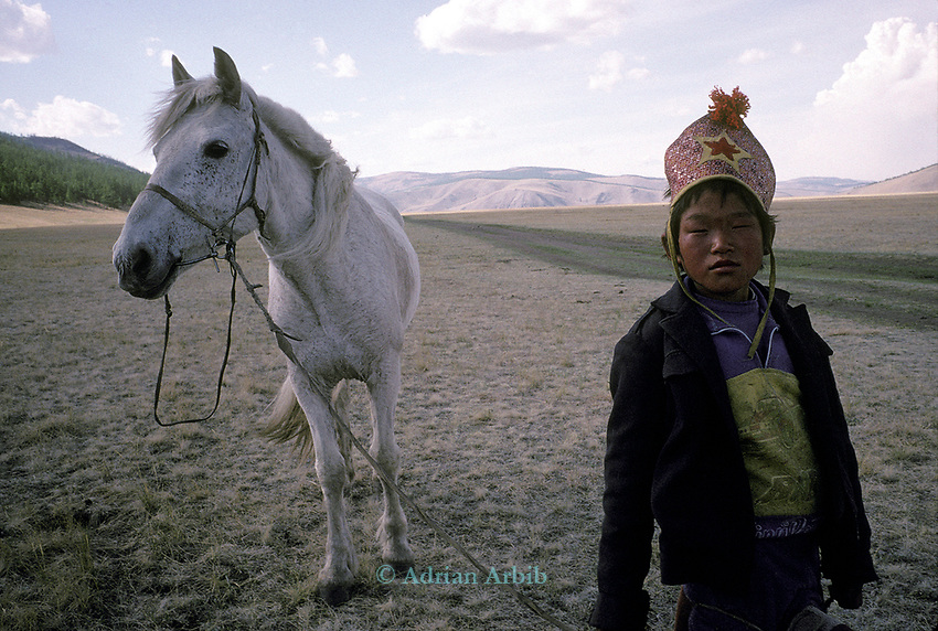 A boy and his horse on their way to  a Naadam festival.    Northern outer Mongolia<br /> <br /> The games are Mongolian wrestling, horse racing, and archery, and are held throughout the country during midsummer. Women have started participating in the archery and girls in the horse-racing games, but not in Mongolian wrestling.