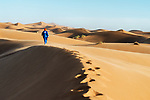 Traditional dressed Moroccan man with turban walks on a sand dune in the Sahara desert.
