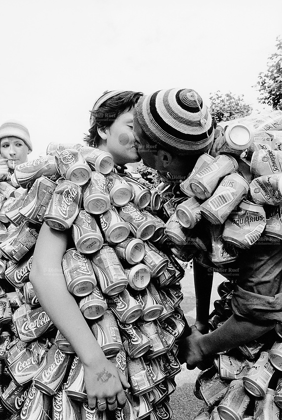 Switzerland. Geneva. A couple kisses during the Lake parade which is a yearly techno event in Geneva. The man and the woman, both are dressed up on their bodies with aluminium cans from Coca Cola, Schweppes and Aquarius. © 2005 Didier Ruef