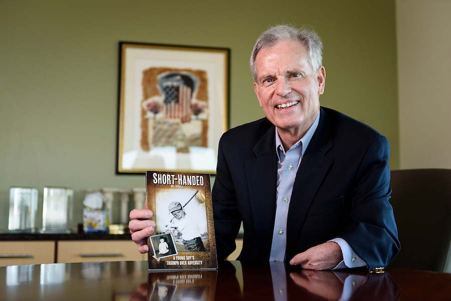 "Bill Schultz, executive recruiter for Sales Consultants of Madison, is pictured in an office conference room in Madison, Wis., on Jan. 23, 2016. Schultz, born with arm and leg deformities, is also author of the autobiographical book, ""Short-Handed: A Young Boy's Triumph Over Adversity."" (Photo by Jeff Miller, www.jeffmillerphotography.com)"