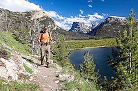 Hiker on a pretty day traveling the Highline Trail that traverses the Wind River Mountains.  Green River Lake and Square Top Mountain, dominate the landscape of the Northern Wind River Mountains