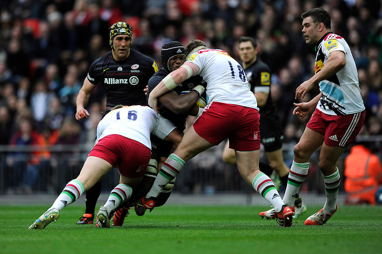 Biyi Alo of Saracens is wrapped up by Rob Buchanan and Matt Shields of Harlequins