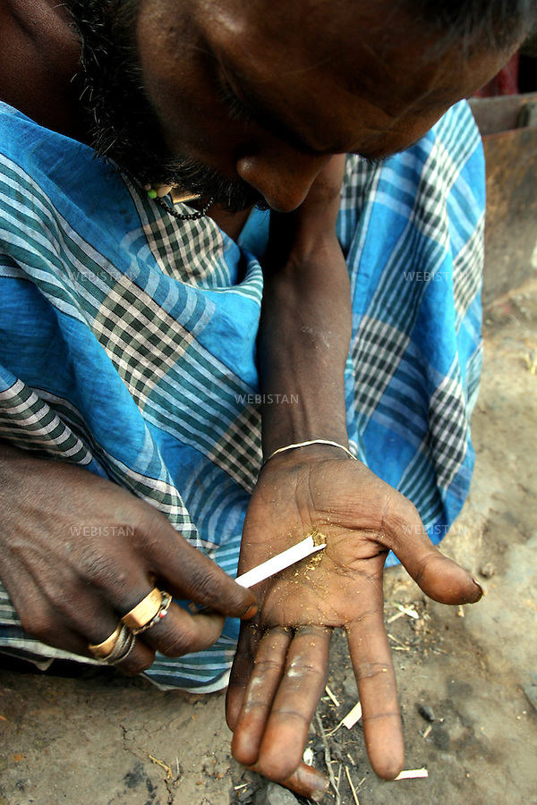 2005. Bangladesh, Dhaka. A man fills a cigarette with marijuana. .Such ready-made joints are available nearly everywhere in Dhaka, even in front of many police stations..2005. Bangladesh, Dhaka. Un homme remplit une cigarette de Marijuana..Ces joints tout prêts se trouvent à peu près partout à Dhaka, même devant de nombreux postes de police