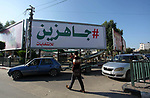 """Palestinians walk past a mural titled """"ready for Elections"""" in Gaza city, on October 29, 2019. Gaza's Hamas leaders say they're ready to hold Palestinian elections – a potentially significant step that could help end a 12-year rift with the rival Palestinian Authority. Photo by Mahmoud Ajjour"""
