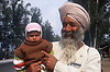 Elderly man with full white beard holding young child,