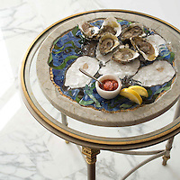 Hand-cut pieces of Calcatta and Lavastone create the oysters in this tray, a beveled finish is applied to form an indentation for the shells to rest in. 24K gold glass accents tie together the aquatic background made up of Malachite, Aventurine, Blue Spinel, all of which is inlaid in a frame of Seagrass marble