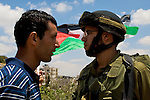 A Palestinian demonstrator faces off with an IDF soldier during a demonstration against Israel's controversial separation barrier in the West Bank town of Beit Jala near Bethlehem on 27/06/2010.