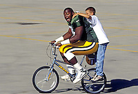 An unidentified Green Bay Packer rides a boy's bike downhill to the Ray Nitschke practice field in 1996.<br />