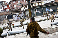 Soldiers from the Central Reserve Police Force (CRPF) and Jammu and Kashmir Police are chased away by the protesters during a protest in downtown Srinagar, the day after Kashmir went to the polls in the Indian national elections.
