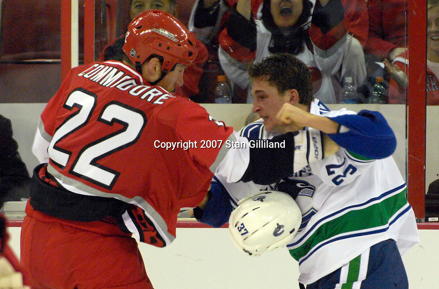 Carolina Hurricanes defenseman Mike Commodore and the Vancouver Canucks' Rick Rypien (37) square off during their game Monday, Oct. 22, 2007 in Raleigh, NC. The Hurricanes won 3-1.