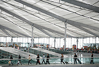 Travelers enter the departure lounge of the futuristic South Railway Station through a glass walkway in Shanghai, China. With the Chinese New Year only one week away, millions of Chinese are traveling in hopes of spending this most important of traditional Chinese holidays with their family..9 Feb 2007