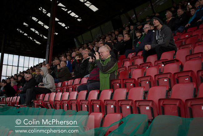 Home supporters in the main stand watching the second-half action at The Oval, Belfast as Glentoran host city-rivals Cliftonville in an NIFL Premiership match. Glentoran, formed in 1892, have been based at The Oval since their formation and are historically one of Northern Ireland's 'big two' football clubs. They had an unprecendentally bad start to the 2016-17 league campaign, but came from behind to win this fixture 2-1, watched by a crowd of 1872.
