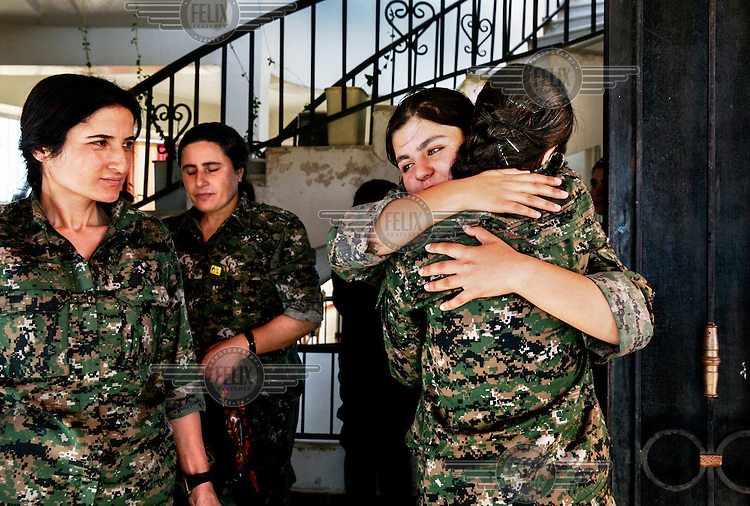 Comrades welcome each other, after returning from the front lines, at the YPJ's (Women's Protection Unit) compound. The YPJ is a Kurdish female militia fighting the Islamic State and Jabhat al-Nusra in the primarily-Kurdish north. Around 35 percent of the Democratic Union of Kurdistan (PYD)-controlled People's Defense Units (YPG) fighters in Syria are women.