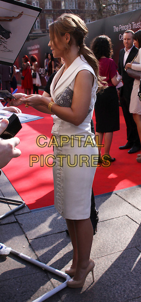 KIMBERLEY WALSH  .The Prince's Trust Celebrate Success Awards at Odeon Leicester Square,  London, England..March 23rd, 2011.full length dress signing autographs profile side ponytail white sleeveless grey gray clutch bag .CAP/AH.©Adam Houghton/Capital Pictures.
