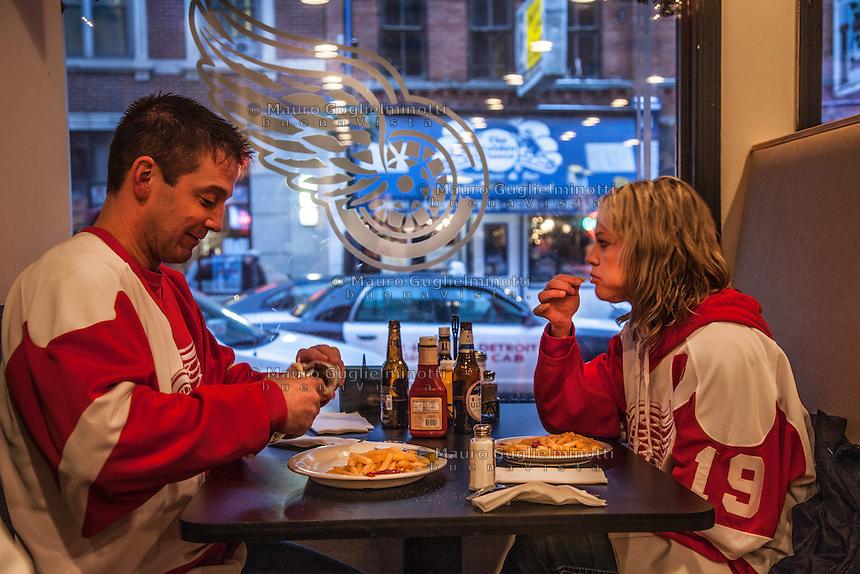 Una coppia  seduta ad un fast food di Detroit, sullo sfondo il logo dei Detroit Red wings, squadra di hockey su ghiaccio
