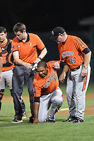 Aberdeen IronBirds trainer Chris Poole and manager Matt Merullo (27) help pitcher Ivan Hernandez (38) after getting hit in the head by a broken bat during a game against the Williamsport Crosscutters on August 4, 2014 at Bowman Field in Williamsport, Pennsylvania.  Aberdeen defeated Williamsport 6-3.  (Mike Janes/Four Seam Images)