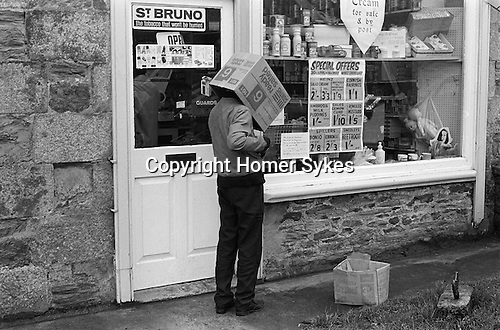 Young boy with empty cardboard box of Ready Salted Crisps over his head outside a village shop Cornwall. 1971