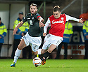Partick's Sean Welsh and Dundee Utd's Paul Paton challenge for the ball.