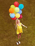 Happy young woman in yellow summer dress flying up from the ground with colorful helium balloons, retro stylized photo.