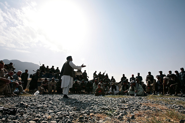 Niaz Mohammad Sarahadi, governor of Zhari district, in Kandahar province, Afghanistan urges a crowd of men near the village of Ashoque to cooperate with NATO and Afghan troops in the fight against the Taliban. U.S. and Canadian soldiers have built a series of small outposts in Zhari and other districts west of Kandahar, in an effort to improve security in the city and stem the worsening insurgency. But it remains far from clear how the fight will turn out in Zhari and other nearby districts which are traditional Taliban strongholds. Nov. 23, 2009. DREW BROWN/STARS AND STRIPES