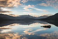 Sunrise over Lake Kaniere near Hokitika with perfect reflections and Toaroha Ranges in background, West Coast, South Westland, New Zealand
