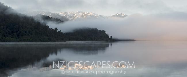 Sunrise fog reflections on Lake Mapourika with Mount Tasman of Southern Alps on horizon, Westland Tai Poutini National Park, West Coast, UNESCO World Heritage Area, New Zealand, NZ