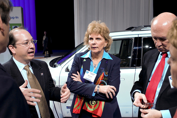 "WASHINGTON, DC - Jan. 22: Sue Cischke, senior vice president of Sustainability, Environment and Safety Engineering for Ford, shows off a plug-in Ford Escape to Assistant Energy Secretary Alexander ""Andy"" Karsner, far left, and former CIA Director R. James Woolsey, far right, during media day at the Washington Auto Show. At left is a hybrid Escape, at middle background is a flex fuel F150; at right is a plug in hybrid Escape. (Photo by Scott J. Ferrell/Congressional Quarterly)"