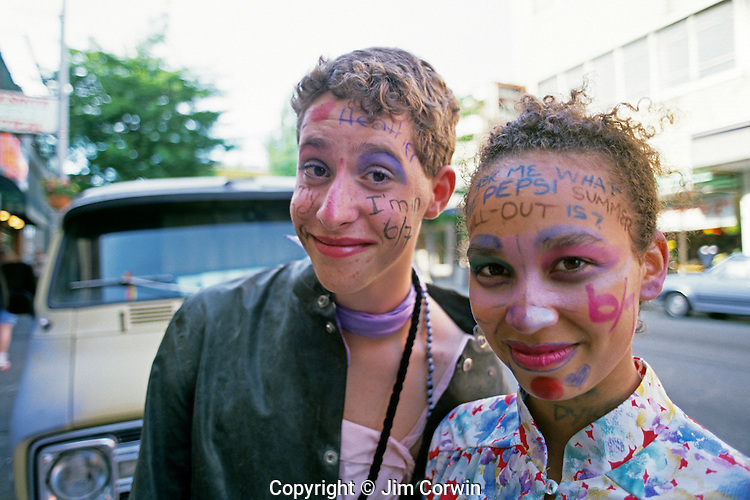 "Young woman and boy along the ""Ave"" smiling with faces painted with words University District Seattle Washington State USA"