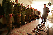 The last draft. Soldeirs gathering for early morning assembly, with AK-47 Kalashnikov rifles laid out on the floor. <br />