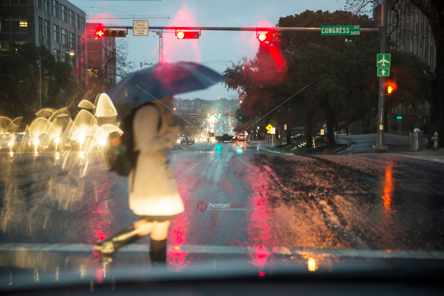 A State of Texas Capitol government worker holding a umbrella during a rain storm crosses Congress Avenue in downtown Austin, Texas.