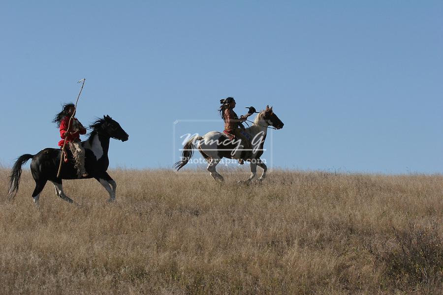 Two Native American Indians riding horseback looking for ememies through the prairie of South Dakota