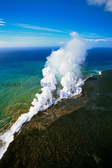 Aerial view of the coastline at Kilauea showing hot molten lava creating massive steam clouds as it enters the ocean, Hawaii Volcanoes National Park, Kilauea, Big Island, Hawaii, Pacific Ocean.
