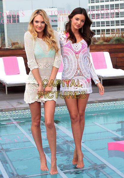 Candice Swanepoel, Miranda Kerr.Victoria's Secret Celebrates its 2012 Swim Collection held at the Thompson Hotel in Beverly Hills, Beverly Hills, California, 29th March 2012..full length models  white crochet dress walking on water standing in swimming pool pink bikini rooftop roof underwater runway .CAP/ADM/SLP/JO.©James Orken/Starlitepics/AdMedia/Capital Pictures.