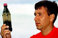 O capitão do corpo de bombeiros Claudio Tavernard, mostra a amostra de oleo retirada do fundo do rio, onde percebeu a abertura entre os sacos de areia possibilitando que o oleo se espalhasse.<br />08/03/2000. Foto Paulo Santos/Interfoto